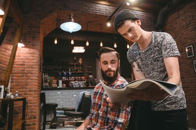 Jonge kapper en aantrekkelijke bebaarde klant die door tijdschrift kijkt terwijl hij in de kapperszaak zit