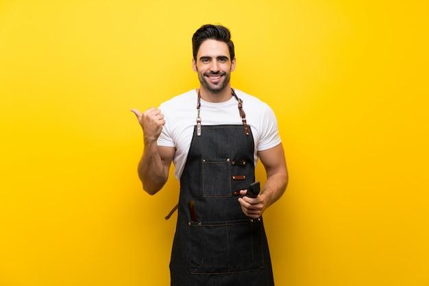 Jonge kapper man over geïsoleerde gele wijzend naar de kant om een product te presenteren