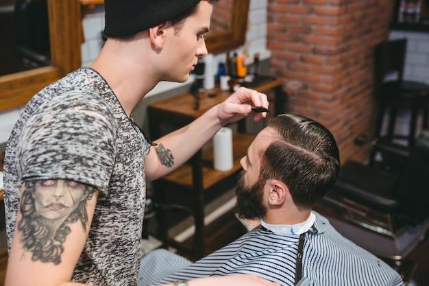 Jonge kapper met tatoeage die haar van mannelijke cliënt kamt met een kam in kapsalon