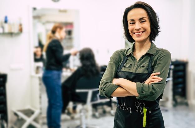 Jonge kapper. portret van professionele haarstylist die in de camera kijkt en lacht met gevouwen armen, staande in de buurt van een klant die haar haar laat doen.