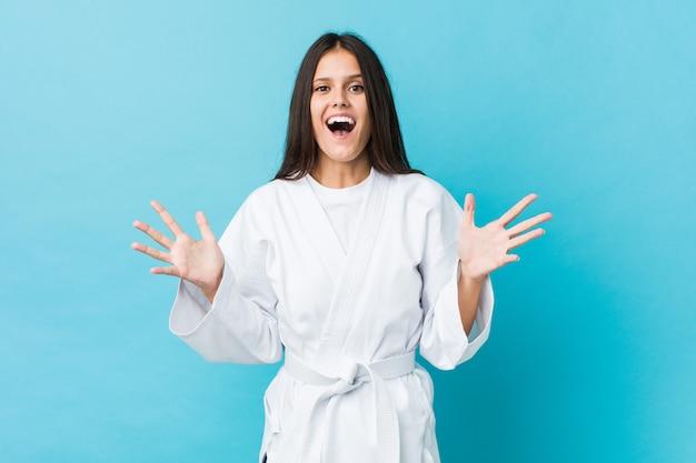 Jonge karatevrouw die een overwinning of een succes vieren
