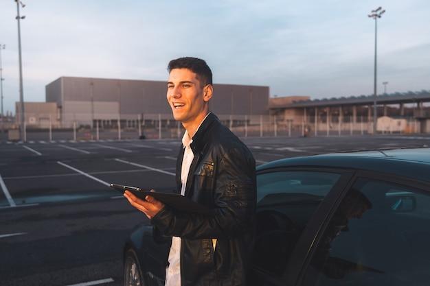 Jonge kaukasisch met behulp van een digitale tablet met een sportwagen achter op een parkeerplaats.