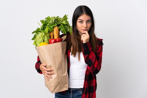 Jonge kaukasisch met groenten die bij het witte denken worden geïsoleerd