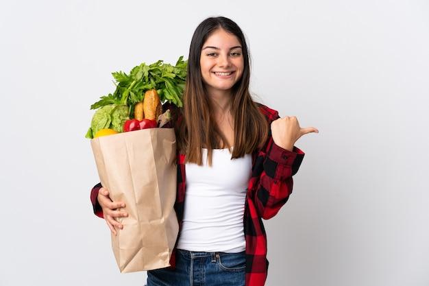 Jonge kaukasisch met groenten die op wit worden geïsoleerd dat naar de kant wijst om een product te presenteren