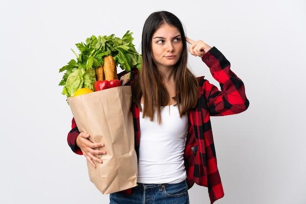 Jonge kaukasisch met groenten die op wit worden geïsoleerd dat twijfels heeft en denkt
