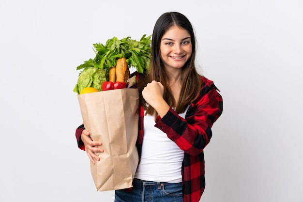 Jonge kaukasisch met groenten die op wit worden geïsoleerd die een overwinning vieren