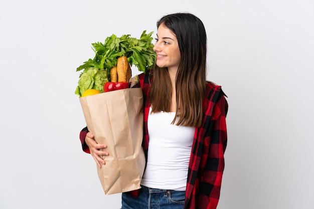 Jonge kaukasisch met groenten die op wit worden geïsoleerdk op zoek naar kant