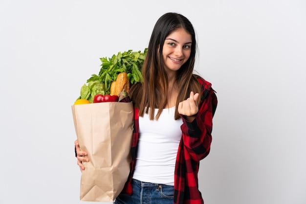 Jonge kaukasisch met groenten die op witte muur worden geïsoleerd die geldgebaar maken