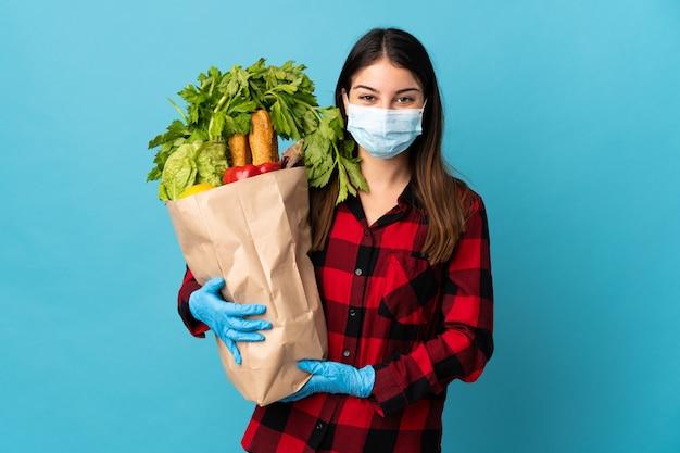 Jonge kaukasisch met groenten en masker dat bij blauw wordt geïsoleerd dat veel glimlacht