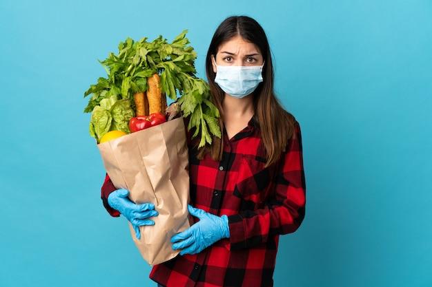 Jonge kaukasisch met groenten en masker geïsoleerd op blauw met droevige uitdrukking