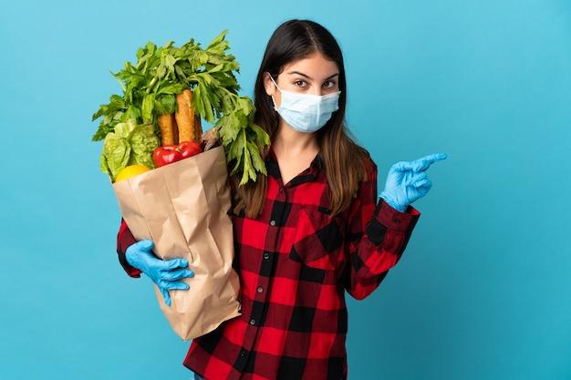 Jonge kaukasisch met groenten en masker geïsoleerd op blauw verrast en wijzende vinger naar de zijkant