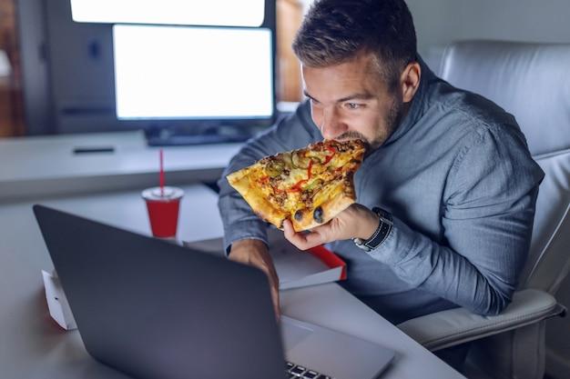 Jonge kaukasische architect die pizza eet op kantoor.