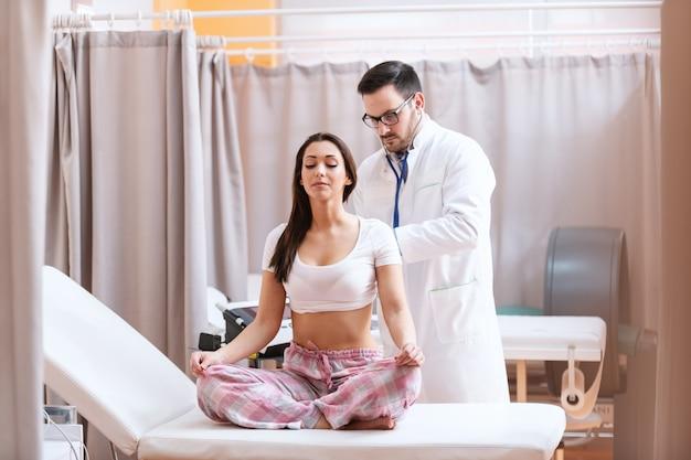 Jonge kaukasische arts die stethoscoop gebruikt om de longen van de patiënt te onderzoeken. patiënt zittend in pyjama met benen gekruist op ziekenhuisbed.