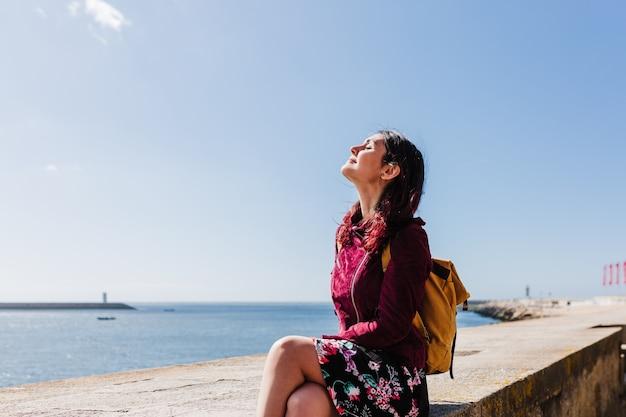 Jonge kaukasische backpackervrouw die porto-meningen door de rivier bezoekt. reis- en vriendschapsconcept