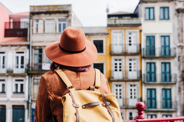 Jonge kaukasische backpackervrouw die porto uitzichten bezoekt. reis- en vriendschapsconcept