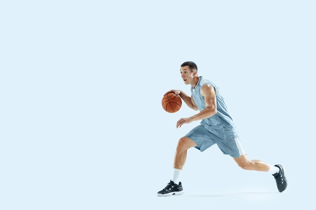 Jonge kaukasische basketbalspeler tegen witte studioachtergrond