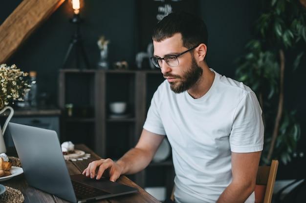 Jonge kaukasische bebaarde man freelancer met behulp van laptopcomputer, thuis werken.