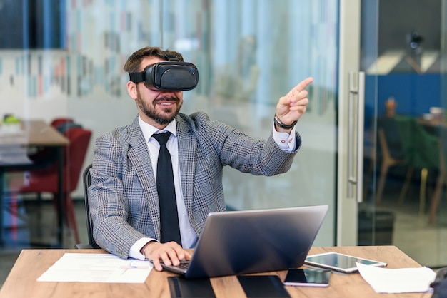 Jonge kaukasische bebaarde zakenman in blauw pak met vr bril op kantoor.