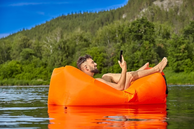 Jonge kaukasische bebaarde zakenman met mobiele telefoon in zijn hand ligt op oranje opblaasbare ligstoel, die op de rivier in de buurt van bos, ecotoerisme zwemt.