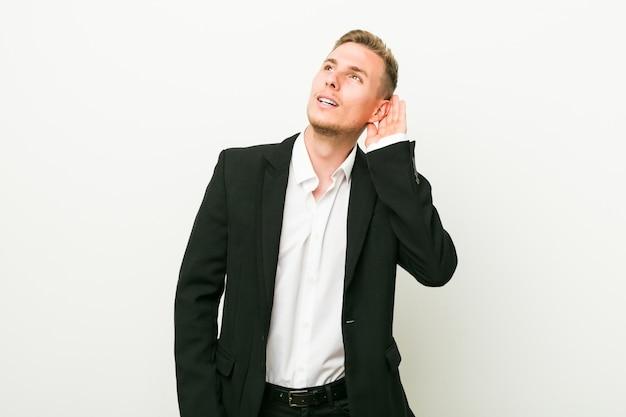 Jonge kaukasische bedrijfsmens die aan een roddel probeert te luisteren.