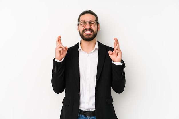 Jonge kaukasische bedrijfsmens die op een witte achtergrond wordt geïsoleerd die vingers kruist voor het hebben van geluk