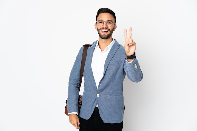 Jonge kaukasische bedrijfsmens die op witte muur wordt geïsoleerd die en overwinningsteken glimlacht toont