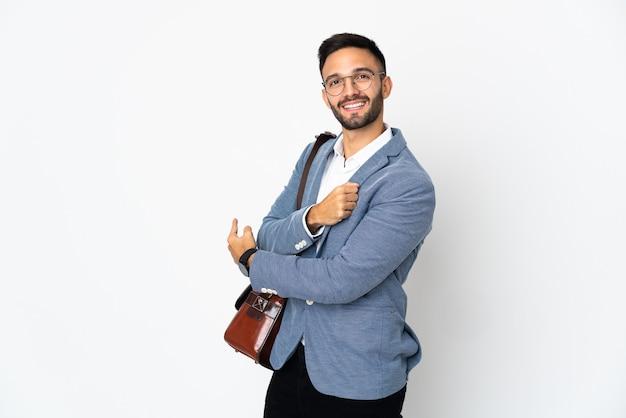 Jonge kaukasische bedrijfsmens die op witte muur wordt geïsoleerd die terug richt