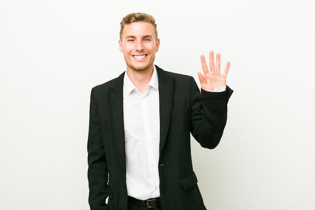 Jonge kaukasische bedrijfsmens die vrolijk tonend nummer vijf met vingers glimlacht.