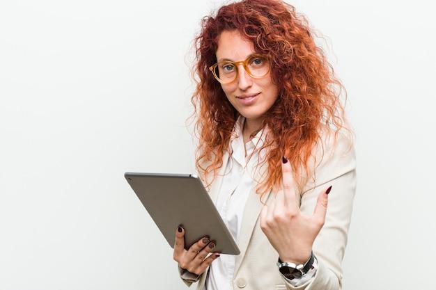 Jonge kaukasische bedrijfsroodharigevrouw die een tablet houden richtend met vinger op u alsof uitnodigend dichterbij kom.