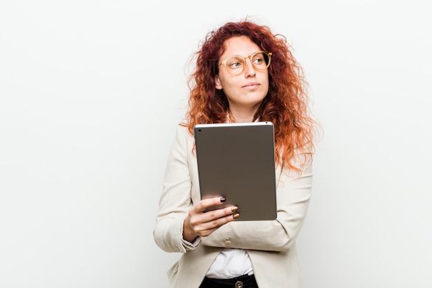 Jonge kaukasische bedrijfsroodharigevrouw die tablet glimlachen houden zeker met gekruiste wapens.