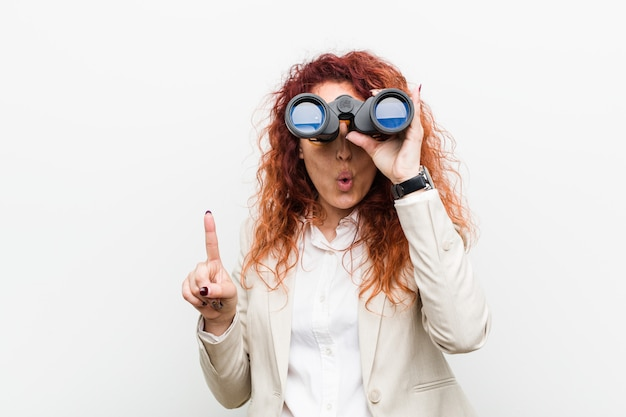 Jonge kaukasische bedrijfsroodharigevrouw die verrekijkers houden die één of ander groot idee hebben