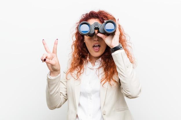 Jonge kaukasische bedrijfsroodharigevrouw die verrekijkers houden die nummer twee met vingers tonen.