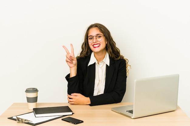 Jonge kaukasische bedrijfsvrouw die aan haar geïsoleerde desktop werken die nummer twee met vingers tonen.