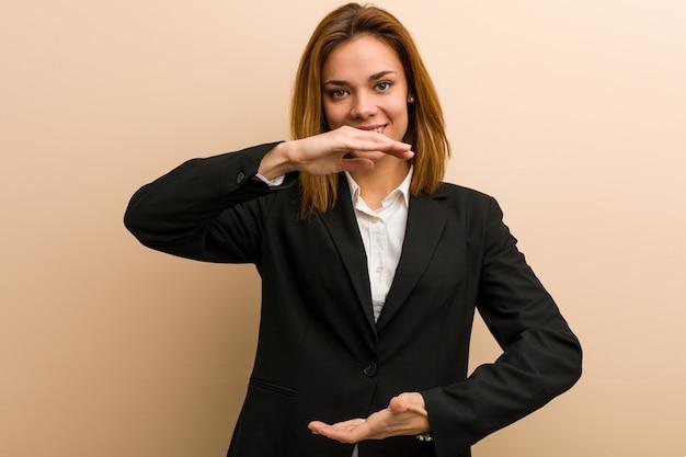 Jonge kaukasische bedrijfsvrouw die iets met beide handen houdt, productpresentatie.