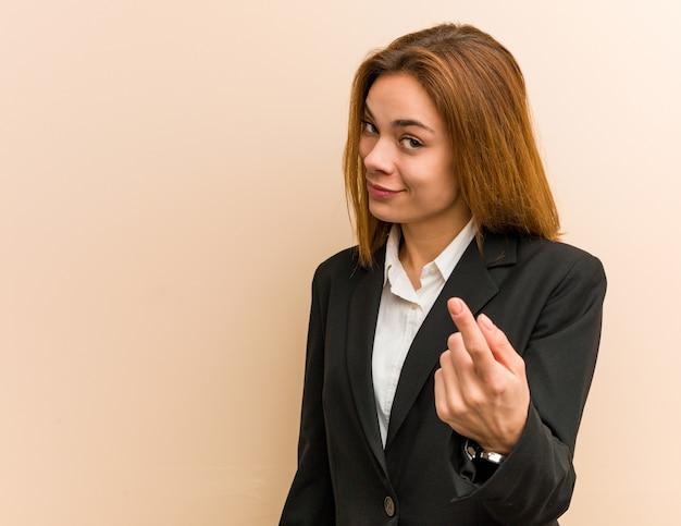 Jonge kaukasische bedrijfsvrouw die met vinger op u richt alsof het uitnodigen dichter komt.