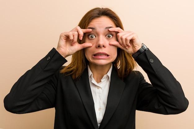Jonge kaukasische bedrijfsvrouw die ogen houdt geopend om een succeskans te vinden.
