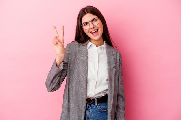 Jonge kaukasische bedrijfsvrouw die op roze muur blij en zorgeloos wordt geïsoleerd die een vredessymbool met vingers toont