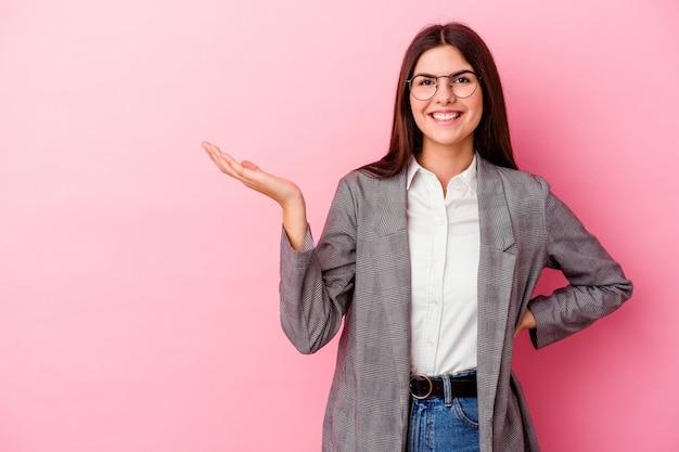 Jonge kaukasische bedrijfsvrouw die op roze muur wordt geïsoleerd die een exemplaarruimte op een palm toont en een andere hand op taille houdt