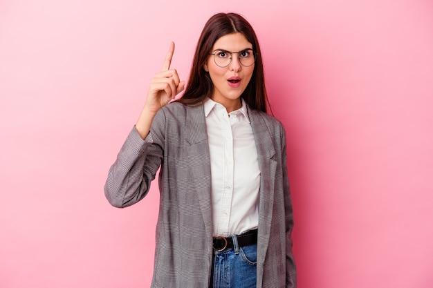 Jonge kaukasische bedrijfsvrouw die op roze muur wordt geïsoleerd die een idee heeft