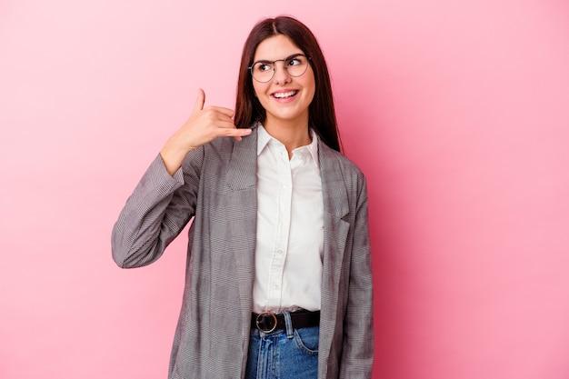 Jonge kaukasische bedrijfsvrouw die op roze muur wordt geïsoleerd die een mobiel telefoongesprekgebaar met vingers toont.