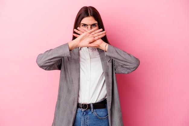 Jonge kaukasische bedrijfsvrouw die op roze muur wordt geïsoleerd die een ontkenningsgebaar doet