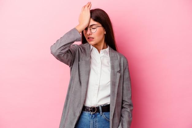 Jonge kaukasische bedrijfsvrouw die op roze muur wordt geïsoleerd die iets vergeet, voorhoofd met handpalm slaat en ogen sluit