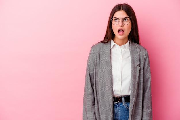 Jonge kaukasische bedrijfsvrouw die op roze muur wordt geïsoleerd die wegens iets dat zij heeft gezien wordt geschokt