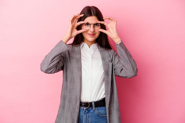 Jonge kaukasische bedrijfsvrouw die op roze ok teken over ogen tonen