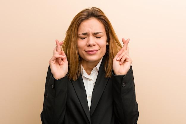 Jonge kaukasische bedrijfsvrouw die vingers kruist voor het hebben van geluk