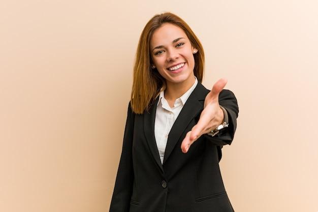 Jonge kaukasische bedrijfsvrouw het uitrekken zich hand bij camera in groetgebaar.