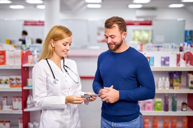 Jonge kaukasische behulpzame vrouwelijke drogist die een mannelijke klant behandelt