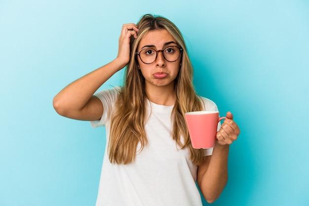 Jonge kaukasische blonde vrouw die een mok houdt die op blauwe achtergrond wordt geïsoleerd die geschokt wordt, heeft zij belangrijke vergadering herinnerd.