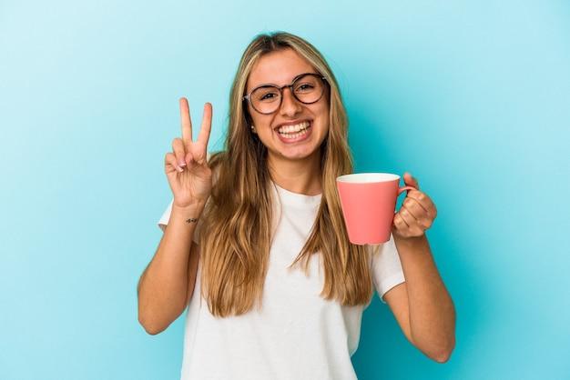 Jonge kaukasische blonde vrouw die een mok houdt die op blauwe achtergrond wordt geïsoleerd die nummer twee met vingers toont.