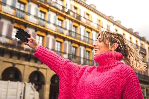 Jonge kaukasische blonde vrouw die een selfie op straat neemt
